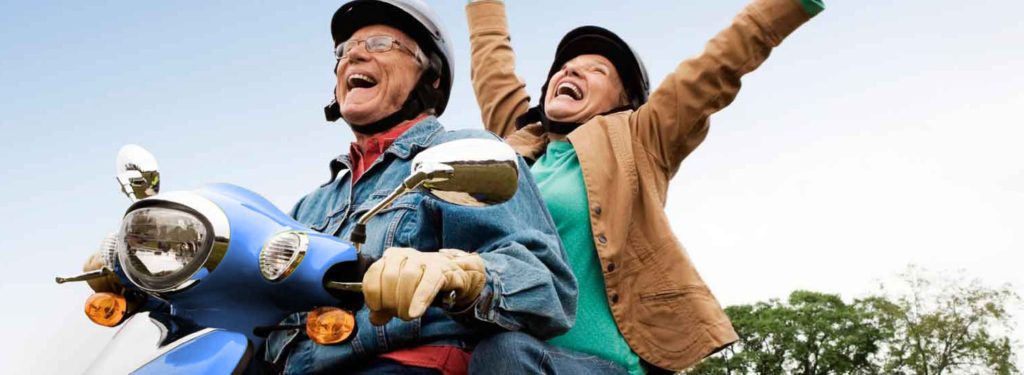 Older man and woman riding a scooter